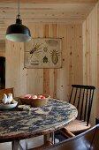 Runder Vintage-Esstisch mit schwarzer Pendelleuchte in holzverkleidetem Zimmer