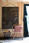 Rattanstuhl mit Kissen und Beistelltischchen vor aufgehängter Vintage-Lerntafel an naturbelassener Holzwand