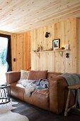 Gemütliche hellbraune Ledercouch mit Kissen, Schaffell und Plaid in holzverkleidetem Wohnraum