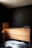 Holz-Badewannentrog vor schwarzer Wand mit schwarz-weißem Schaffell auf schwarzen Boden und Kerzenlicht