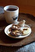 Plätzchen auf Schale mit Porzellan Vogelfigur und Kaffeebecher auf Vintage-Tablett