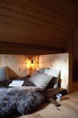 Schlafplatz mit Schaffell vor rustikaler Holzverkleidung