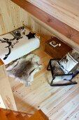 Blick von oben auf Schaukelstuhl und Bett mit Tierfell auf Holzboden