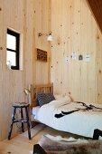 Bett mit nostalgischem Kopfteil und Vintage-Barhocker in holzverkleideter Schlafzimmerecke