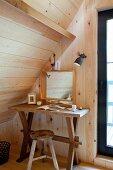 Rustikaler Wandtisch mit Hocker und Spiegel unter Dachschräge in holzverkleideter Zimmerecke