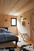 Bett mit karierter Bettwäsche in holzverkleidetem Schlafzimmer, auf Boden schwarz weisses Tierfell