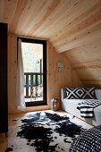 Holzverkleidetes gemütliches Dachschlafzimmer mit schwarzweissem Farbkonzept und Blick auf Balkon