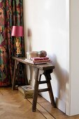 Table lamp with pink lampshade on narrow, antique wooden bench against white wall