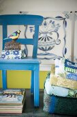 Bird figurine and floral box on blue-painted wooden chair next to stack of towels