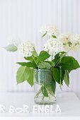 White hydrangeas in glass beaker in front of pale, striped wallpaper and Swedish motto made from alphabet ornaments