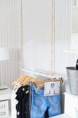 Jeans, tops and baby photo hanging on open clothes rail suspended from ropes