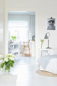 White, shabby-chic living room with view of dining area in kitchen-dining room through open doorway