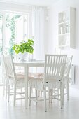 White dining room with frilled cushions on wooden chairs and crockery shelves on wall