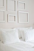 Double bed with white bed linen and stacked pillows below empty, white picture frames on wall