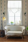 Rococo sofa and simple standard lamp in front of window flanked by wallpapered walls