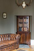Antique, brown leather sofa, glass-fronted cabinet in niche below hunting trophy on wall with patterned green wallpaper