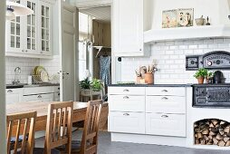 Country-house kitchen with white drawers, cast iron oven and dining area with wooden chairs around table