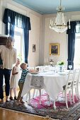 Mother and children in traditional dining room with festively set table below chandelier