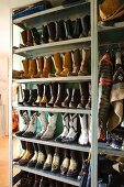 Collection of cowboy boots, leather jacket and cowboy hat on metal shelves in hallway