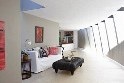 Black ottoman and white, loose-covered sofa on concrete floor in minimalist interior with curved wall