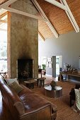Old, brown leather sofa and low, metal table in open-plan interior with fireplace integrated in free-standing wall