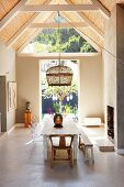 Rustic dining area and wicker pendant lamp below exposed roof structure with bamboo interior cladding
