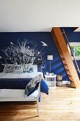Bedroom with dark blue wall, white mural, wooden staircase and bench at foot of double bed