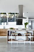 Bar stools at free-standing island counter below extractor hood in open-plan designer kitchen