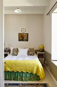 Double bed with yellow blanket and floral valance in simple bedroom