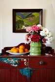 Vase of roses and dish of oranges on farmhouse cabinet with peeling paint on wall below landscape painting