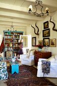 Armchairs with white loose covers, chest of drawers, framed pictures and hunting trophy on wall in rustic living room with white-painted ceiling