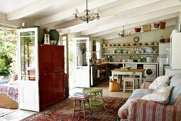 Rustic interior with white, wood-beamed ceiling, couch with scatter cushions opposite open terrace doors and kitchen in background