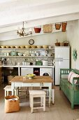 Rustic table and stools and green bench against wall in front of simple kitchen counter in rustic interior