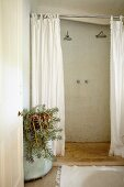 View through open door into rustic bathroom with walk-in shower, white shower curtain and pot of succulents to one side