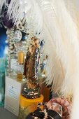 Madonna figurine amongst perfume bottles and white feathers