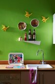 Minimalist kitchen counter with wooden worksurface, metal shelf and flying duck ornaments on wall