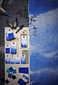 Blue dip-dyed paper gift tags and sheet of paper washed in blue watercolour