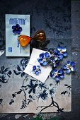 Blue-dyed paper flowers lying on floral paper