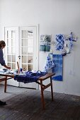 Indigo-blue batik fabric on wall and woman working