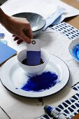 Woman's hand dipping paper gift tag in indigo dye