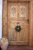 Wreath hung on carved interior door with rustic floor vase to one side