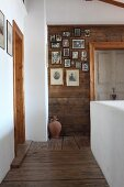 Landing with whitewashed, masonry balustrade and collection of photos on wooden wall