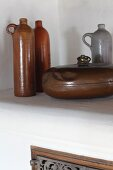 Old stoneware bottles and vintage, metal hot water bottle