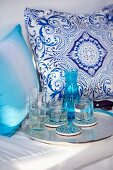 Drinks on tray in front of white and blue patterned cushions on bench