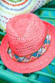 Pink straw hat with patterned hat band on green wicker chair