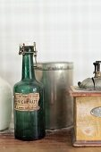 Vintage, swing-top bottle next to old-fashioned coffee mill and tin