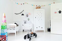 Black, retro-style toy car in white nursery with colourful bunting and stacked toy blocks