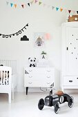 Retro-style, black toy car in white nursery with colourful bunting