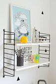 Framed picture and beaker of drinking straws on Sting shelving unit with black sides