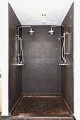 Duschbereich mit dunklen Steinplatten, an Wand zwei Kopfbrausen